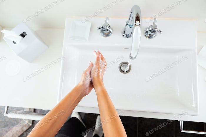 Woman washing hands with soap under the running water from above