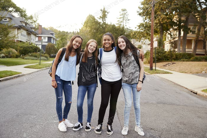 Teen girls on the way to school look to camera, full length