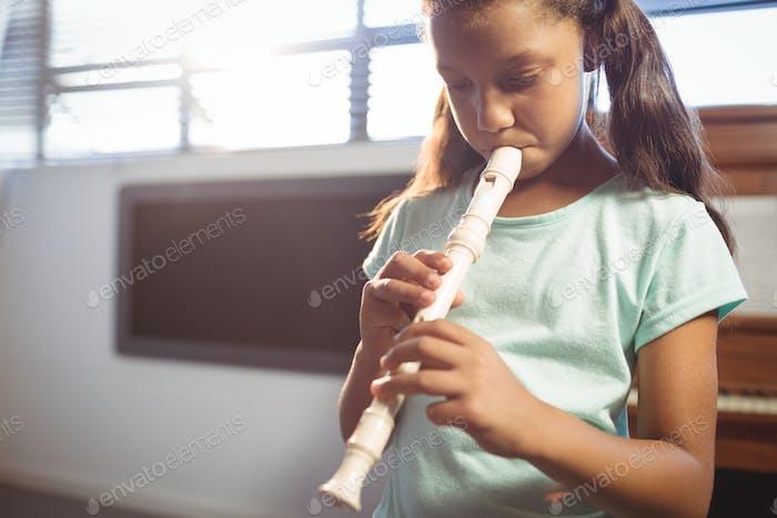 Mädchen üben Flöte in der Klasse