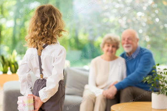 Cute blond child standing with gift behind her back on the grandparent's day