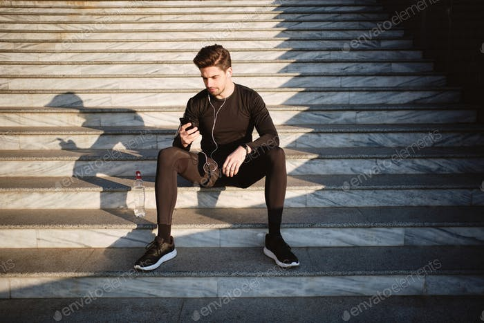Young handsome sporty man sitting on stairs using cellphone after workout outdoor