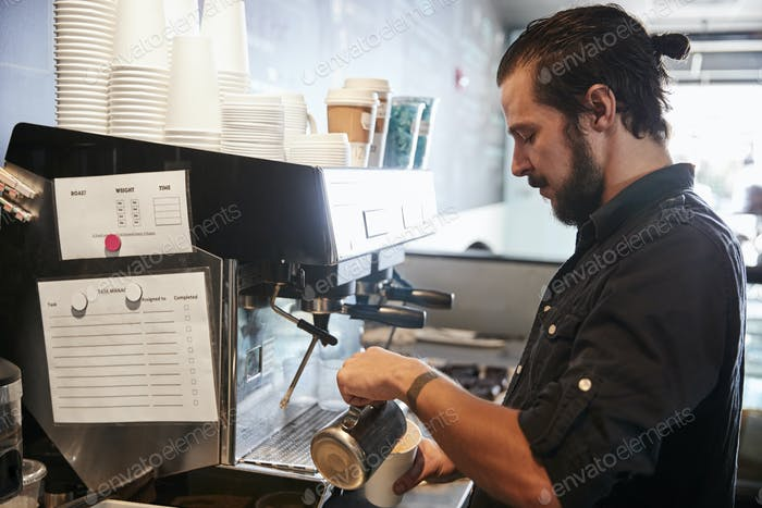 Male Barista Using Coffee Machine Behind Counter In Cafe