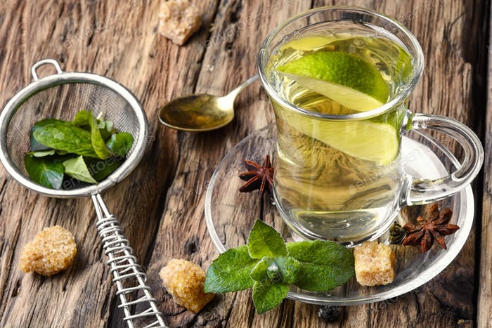 tea brewed with lime and mint on wooden background