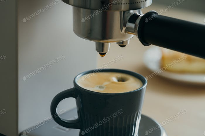 Morning ritual at breakfast with pouring coffee from coffee machine, drops of espresso dripping
