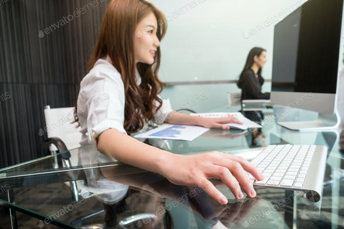 Closeup hand young asian business woman pressing the keyboard of computer for working