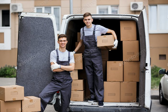 Two young handsome smiling movers wearing uniforms are unloading the van full of boxes. House move