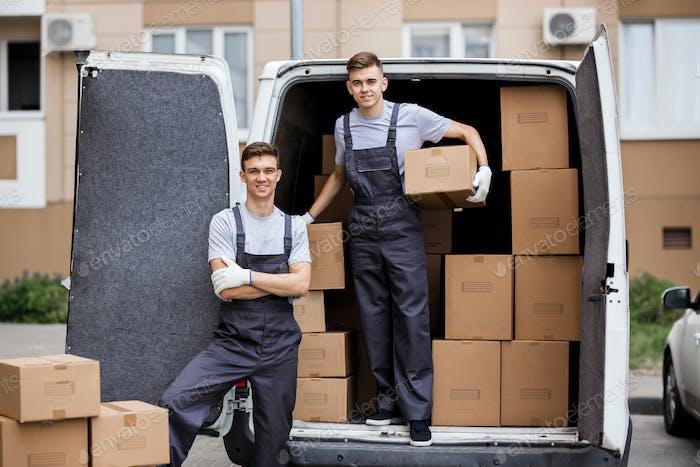 Zwei junge, hübsche lächelnde Mover, die Uniformen tragen, entladen den Van voller Kisten. Haus Umzug