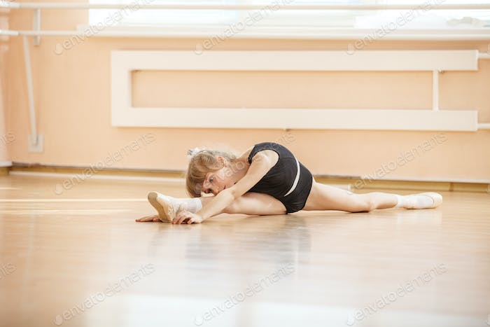 Young girl doing splits while warming up at ballet dance class