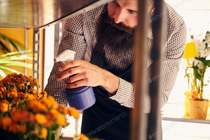 Florista masculino profesional con barba y tatuaje