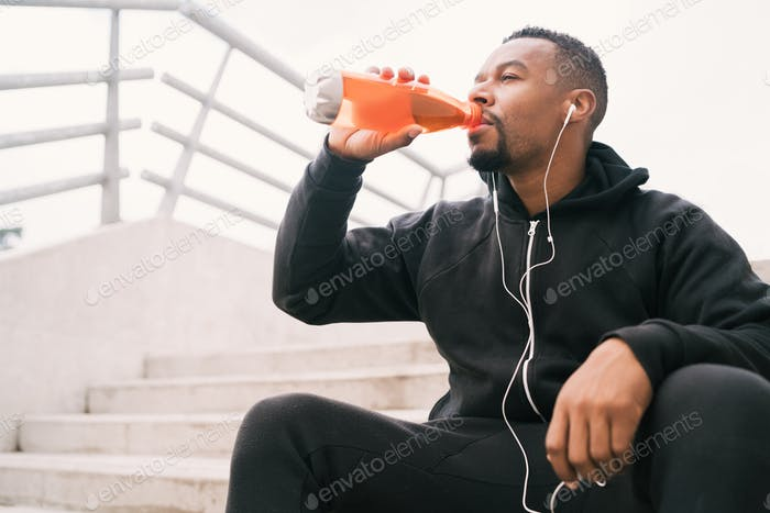 Athletic man drinking something after training.