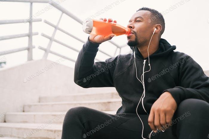 Sportlicher Mann, der nach dem Training etwas trinkt.