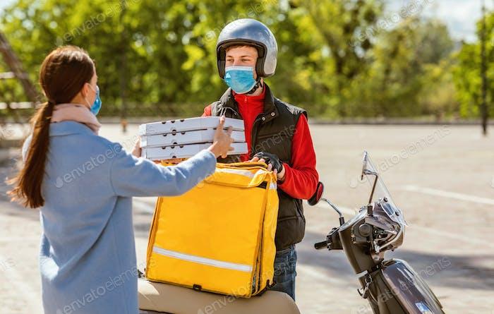 Kurier Giving Pizza-Boxen Frau Tragen Maske Stehen Draußen
