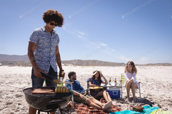 Group friends having fun in preparing a barbecue and chilling together at beach