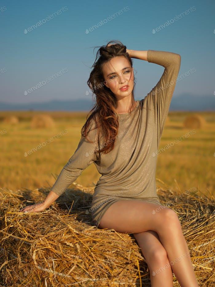 young woman enjoying summer breeze hay stack