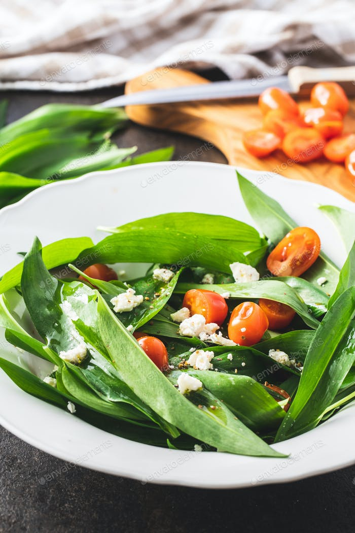 Fresh salad with wild garlic,tomatoes and feta cheese on plate.