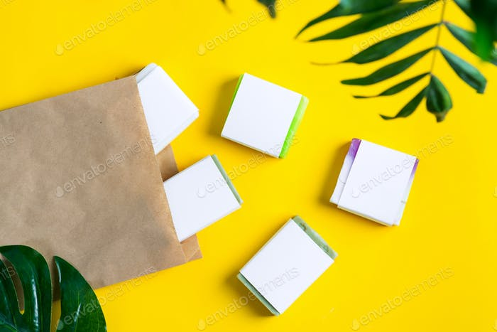 Natural cosmetic handmade soap bar with paper mock-up label and papercraft eco bag on a yellow