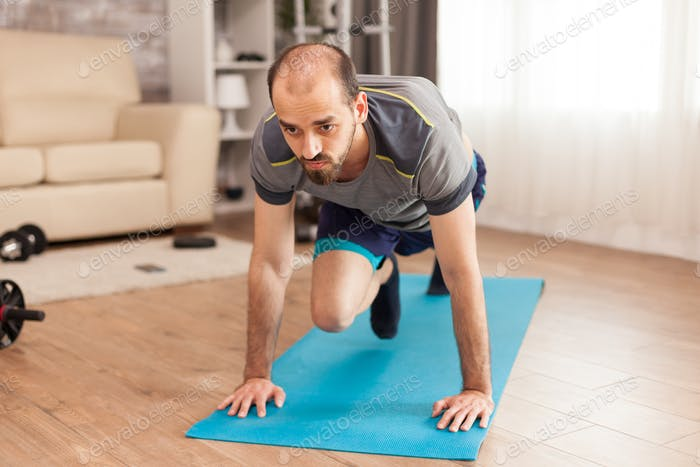 Fit man working his body on yoga mat