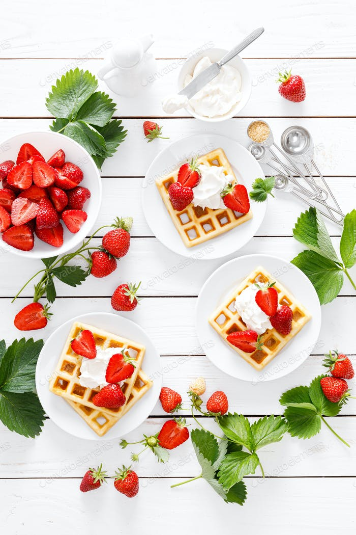 Traditional belgian waffles with cream cheese and fresh strawberry on white background