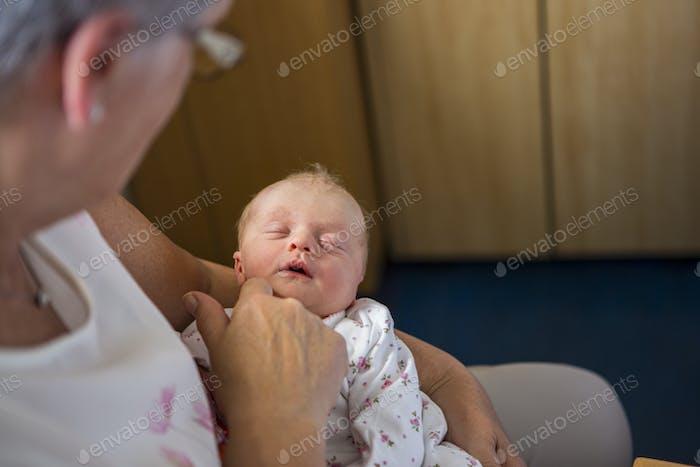 A woman holding sleeping newborn baby