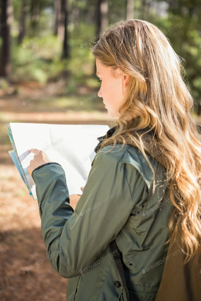 Pretty blonde hiker reading map in the nature