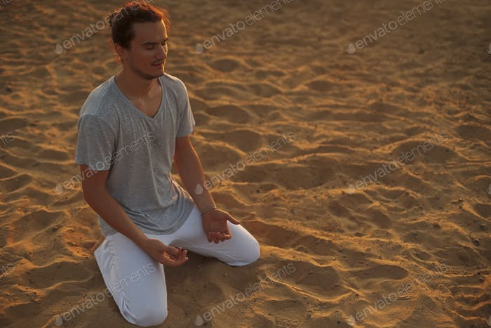 Shot of healthy young man standing in yoga pose on the sand.