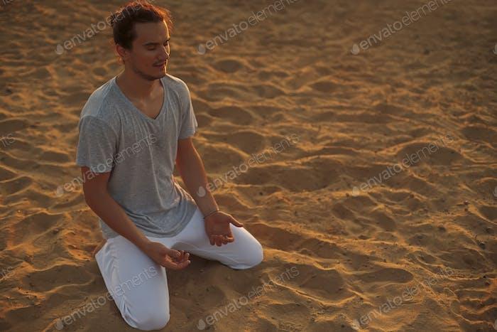 Schuss von gesunden jungen Mann stehend in Yoga-Pose auf dem Sand.