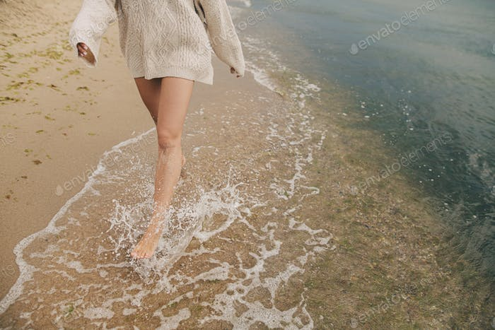 Feet in splashing waves. Carefree woman running barefoot on sandy beach with sea waves. Cropped view