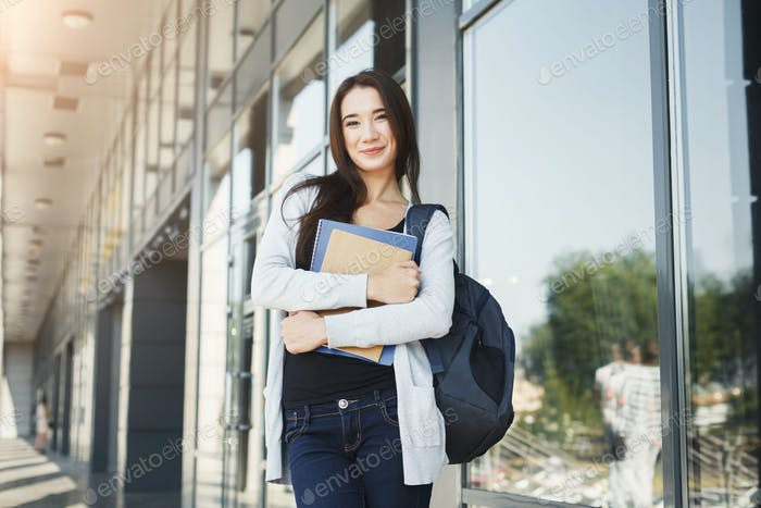 Student girl with books on university background