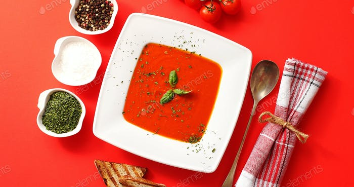Tomato soup served in plate with spoon