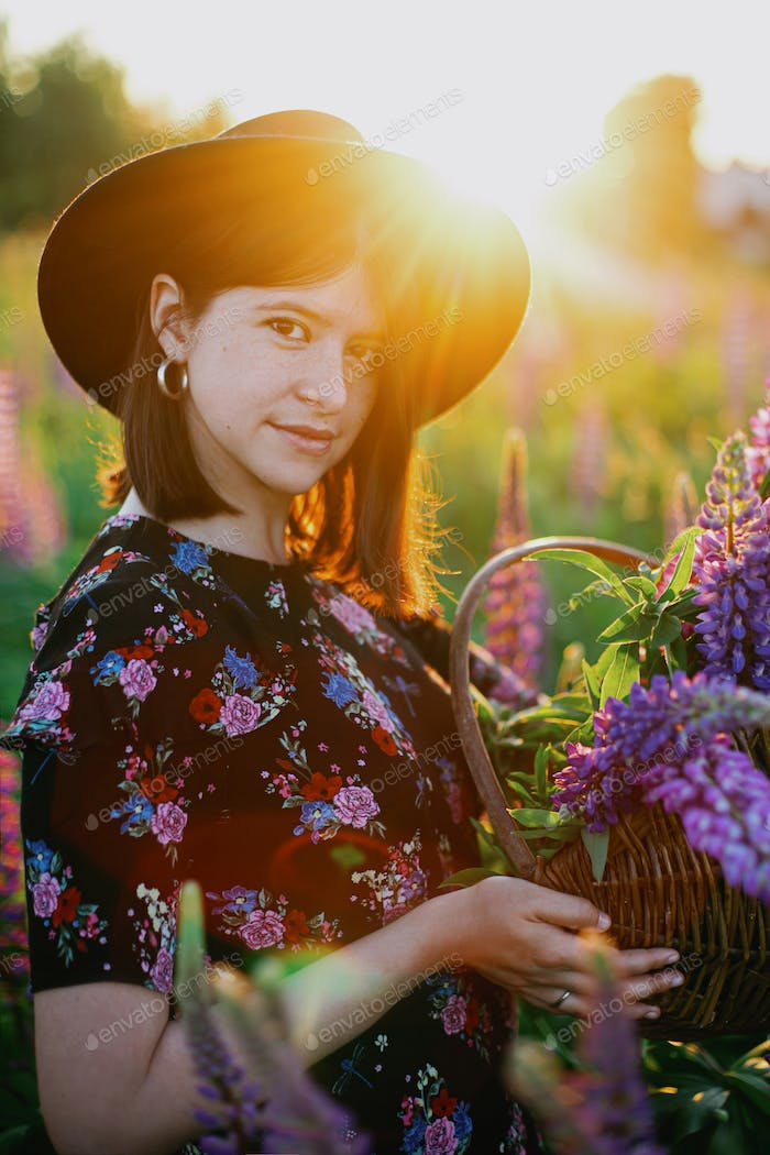 Beautiful woman relaxing in sunny lupine field in countryside meadow at sunset.Atmospheric moment