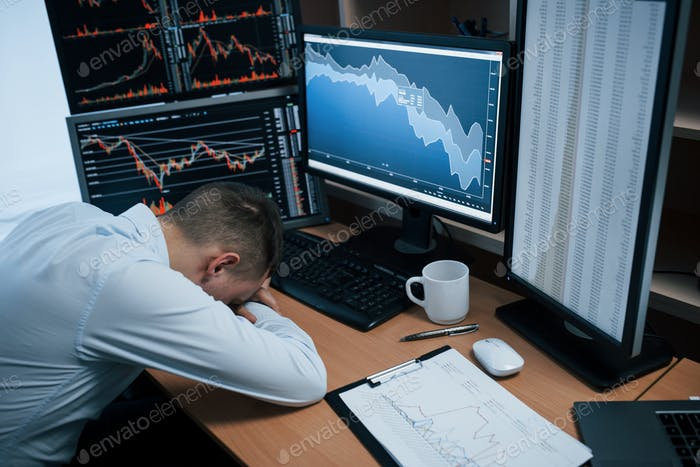 Tired of hard day. Man working online in the office with multiple computer screens in index charts
