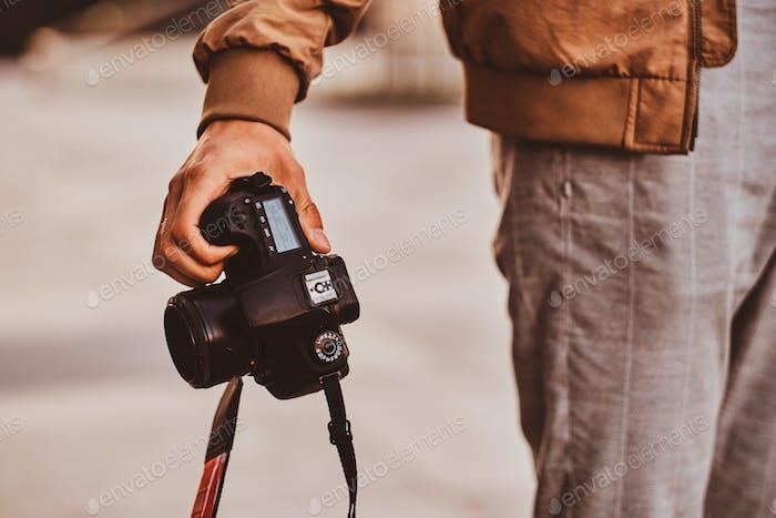 Der Mensch trägt seine digitale Fotokamera