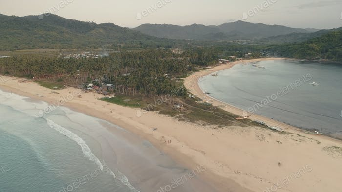 Tropic resort with tourists at sand beach aerial. Ocean coast with resort and lodges buildings