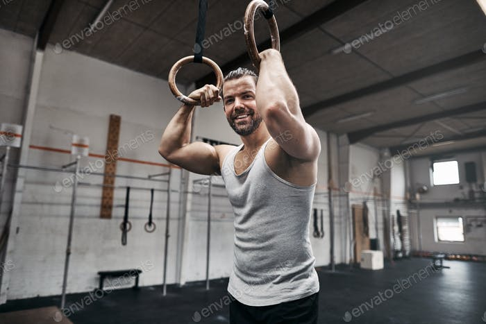 Smiling man resting after exercising on rings at the gym