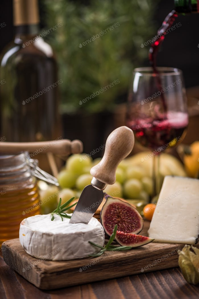 Pouring red wine into glass and serving with camembert