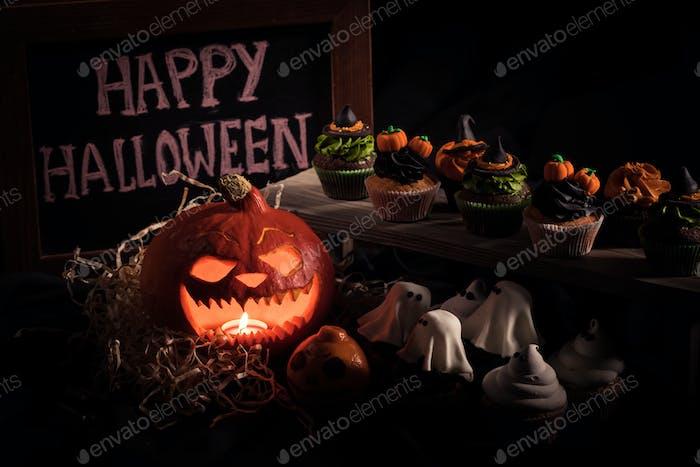Nahaufnahme von Halloween-Cupcakes, Brett mit fröhlicher Halloween-Inschrift und Kürbis mit Kerze