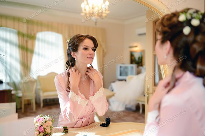 Beauty bride in dressing gown puts on jewel indoors