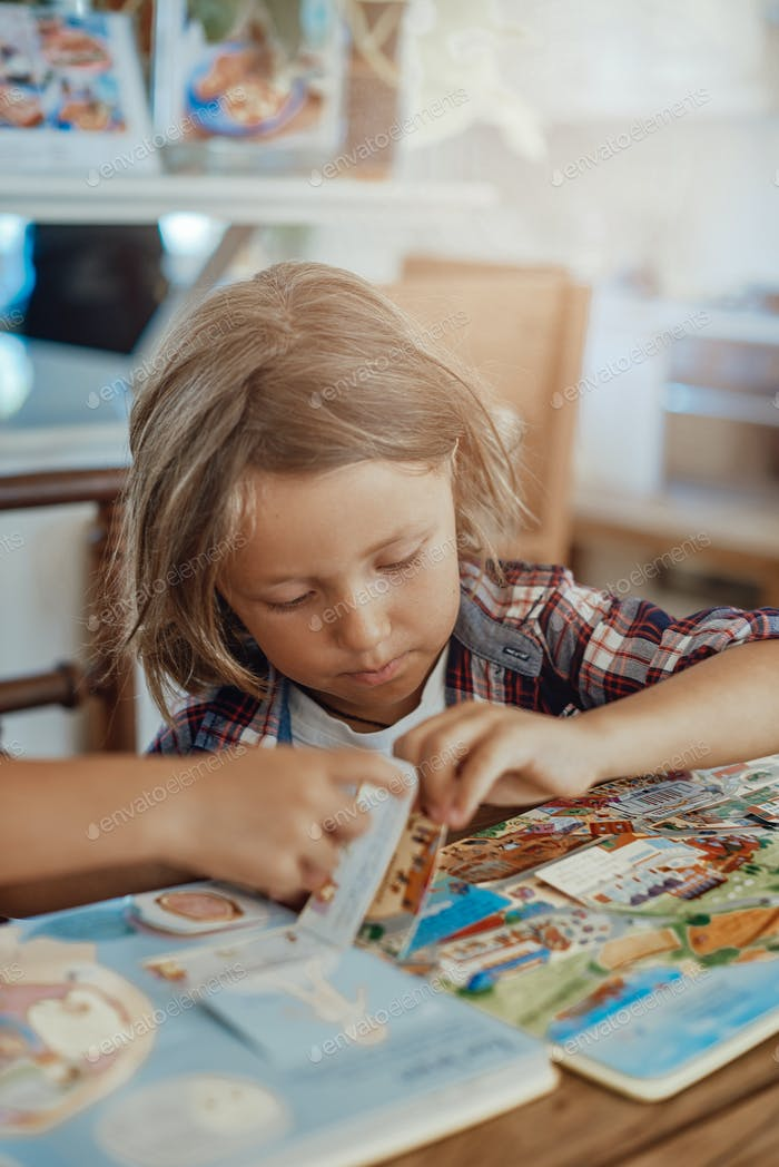 Cheerful kid reads a book at table in lovely and modern living room