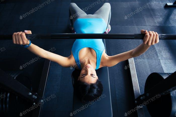 Junge fit Frau arbeiten mit Langhantel auf Bank