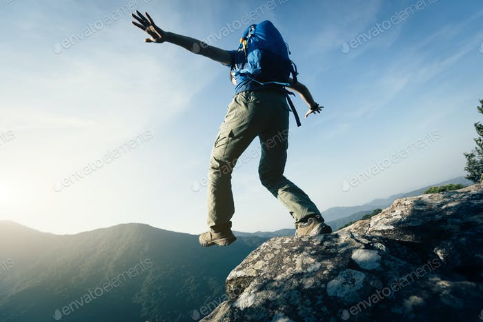 Brave woman backpacker walking to the cliff edge