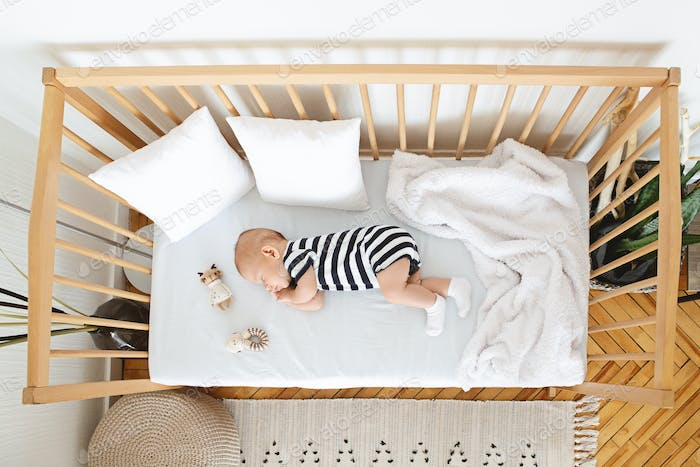 Lovely newborn baby sleeping on his side in wooden crib