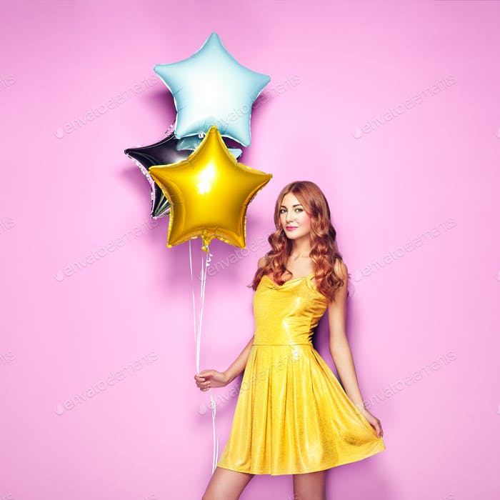 Beautiful young woman with colorful balloons