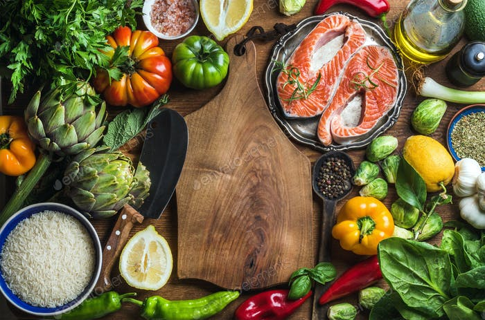Dinner cooking ingredints. Raw uncooked salmon fish with vegetables, rice, herbs and spices