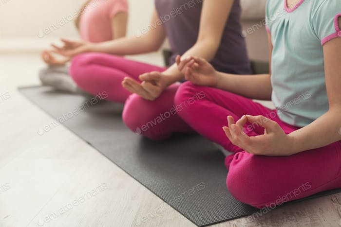 Closeup of mother and daughters hands while doing yoga