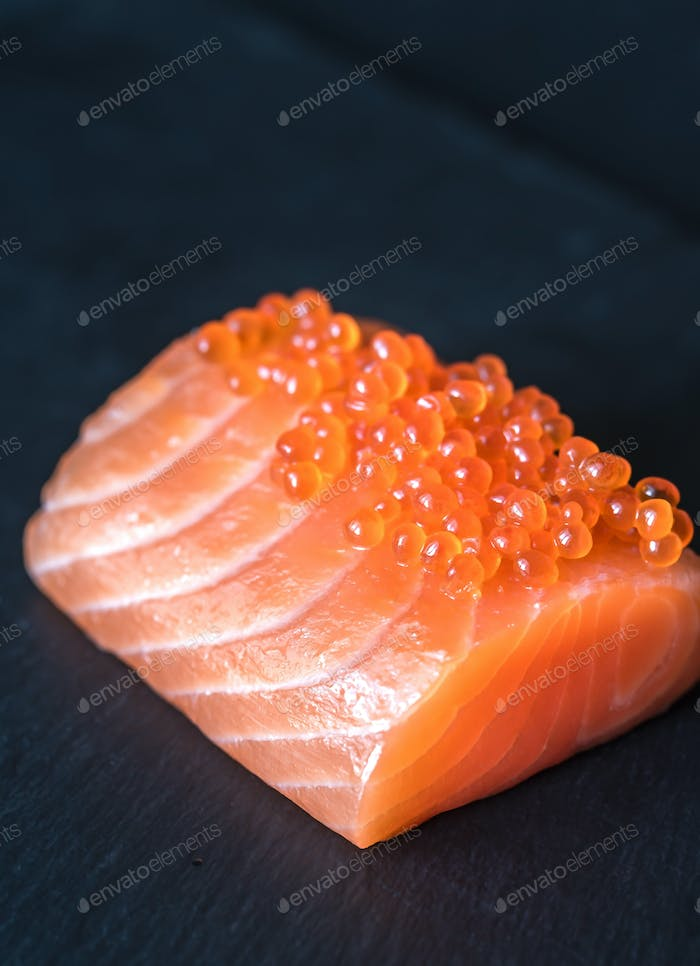 Salmon with red caviar on the black stone board
