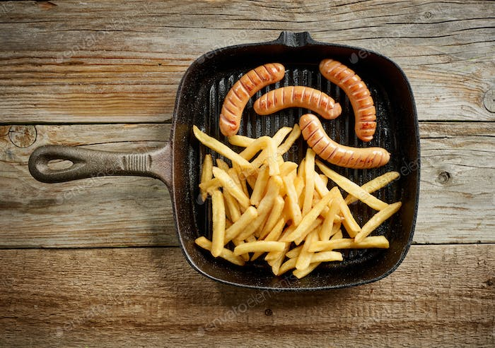meat sausages and fried potatoes on cast iron pan