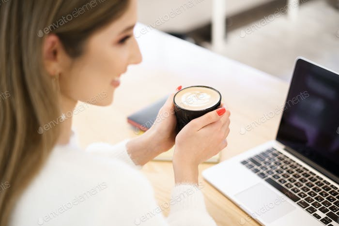 Young female at cafe using laptop and drinking latte