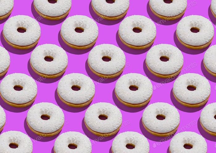 Köstliche Donuts mit weißer zuckerhaltiger Zuckerguss und bestreut über neonvioletten Hintergrund