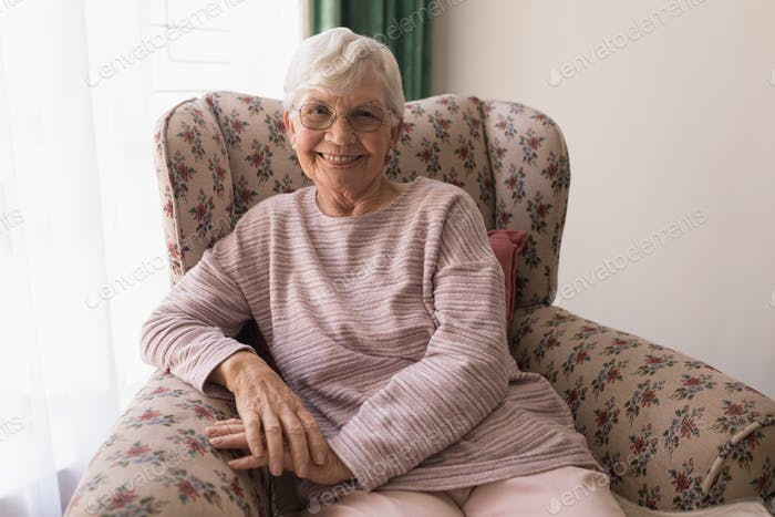 Front view of happy senior woman sitting on the sofa while looking at camera in home