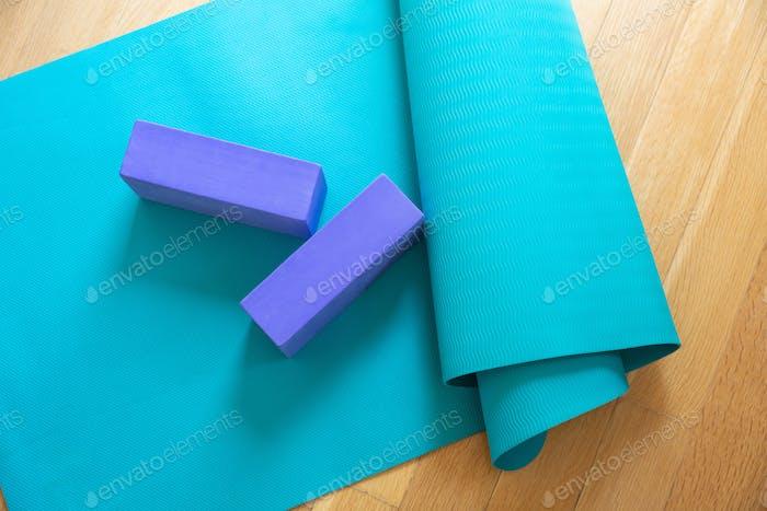 Yoga mat and exercise bricks on wooden floor, pilates yoga class concept